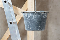 Dirty bucket and ladder on wall background Royalty Free Stock Images