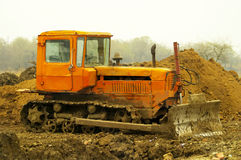 Dirty bulldozer. Dirty orange old locked bulldozer standing on the ground Stock Photography