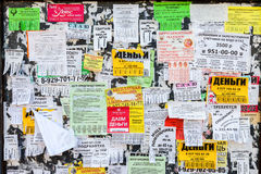 Dirty bulletin board filled with paper notices on russian langua Royalty Free Stock Image