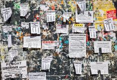 Dirty bulletin board filled with paper notices on russian Royalty Free Stock Photo