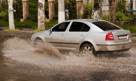 Dirty car. Rides through deep puddle Stock Images