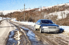 Dirty car on the road. Winter snowfall Royalty Free Stock Images