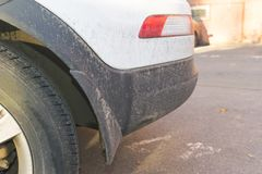 Dirty car side. Fragment of a dirty SUV. Dirty rear wheel and bumper of the off-road car with swamp splashes on a side panel. Dirty car side. Fragment of a Royalty Free Stock Image