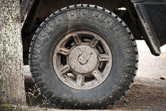 Dirty car wheel stands on rural road Royalty Free Stock Images