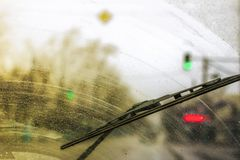 Dirty car windshield with the included glass cleaner, in the big city front and back of the background is blurred royalty free stock image