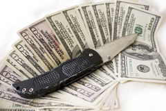 Dirty Cash and Knife. A knife and some fanned out cash laying on a bed. This works for all sorts of illegal activities such as prostitution, drug dealing, and stock image