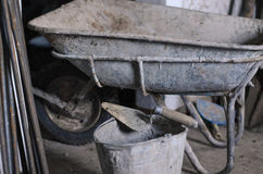 Dirty cement wheelbarrow cart at construction site with unfinished cement wall background. Stock Photo