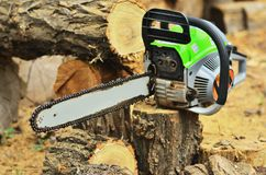 The dirty chainsaw is lying on the hemp. And threes royalty free stock image