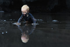 Dirty child crawling on wet black sand beach. On flat ocean beach dirty baby crawling with fun on wet black sand to sea surf for swimming in waves. Family Royalty Free Stock Photos