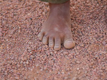 Dirty children`s foot is in the desert sand Royalty Free Stock Photography