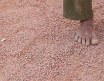 Dirty children`s foot is in the desert sand Royalty Free Stock Photo
