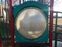 Dirty circular plastic window on play structure at playground. Or park stock photos