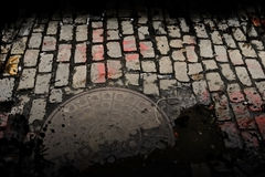 Dirty City Street. Dirty cobblestone street with manhole cover in New York Royalty Free Stock Photo