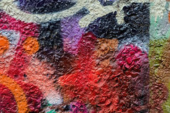 Dirty city wall, spattered with colorful patches of bright colors aerosols. Fragment for background, urban culture Royalty Free Stock Images