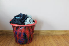 Dirty clothes in red basket on wood floor Royalty Free Stock Photography