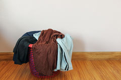 Dirty clothes in red basket on wood floor for washing Royalty Free Stock Image