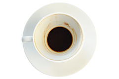 Dirty coffee cup with coffee grounds. On a plate, white background Stock Photo