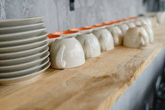 Dirty Coffee cups on wooden shelf. Royalty Free Stock Photography