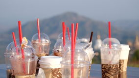 Dirty Coffee take away cups with distant mountains. Stock Image