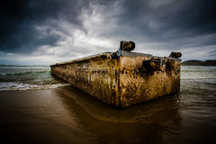 Dirty concrete box washed ashore. Large, dirty concrete or steel box on a sandy beach under threatening skies royalty free stock images