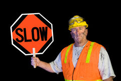 Dirty construction worker holding slow sign. A dirty, greasy utility construction worker with a yellow hard hat, safety goggles, and a reflective orange vest royalty free stock photos