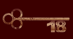 Dirty Copper 18 Key. An eighteenth birthday key in brass and grunge over brown Stock Image