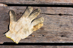 Dirty cotton work glove on the wooden floor Stock Photos