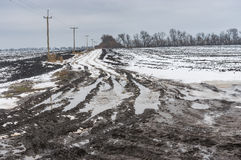 Dirty country road between agricultural fields in central Ukraine at gloomy winter day Stock Photography