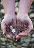 Dirty cupped hands holding few coins Stock Photos