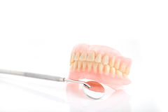 Dirty dentures,Tatar on dentures and dental mirror on white background Stock Images