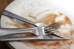 Dirty dinner plates and cutlery ready to be washed up Royalty Free Stock Photos