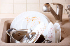 Dirty dishes. Pile of dirty dishes like plates, pot and cutlery in the light beige granite sink Stock Photos