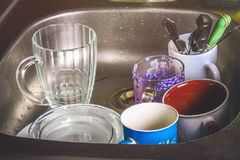 Dirty dishes in foam in the sink waiting for washing. Mugs, plates, cutlery. Stock Photo