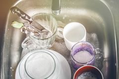 Dirty dishes in foam in the sink waiting for washing. Mugs, plates, cutlery. Royalty Free Stock Photo