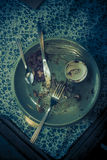 Dirty dishes with fork and knife on a green plate Stock Images