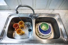 Dirty dishes in kitchen sink. Dirty dishes in metallic kitchen sink at home stock images