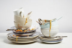 Dirty dishes pile needing washing up on white background royalty free stock image