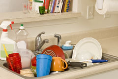 Dirty dishes in sink. Kitchen sink piled high with dirty dishes and bottles of wash detergent Royalty Free Stock Image