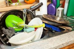 Dirty dishes in the sink after family celebrations. Home cleaning the kitchen. Cluttered dishes in the sink. Housework. Stock Photo
