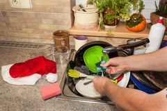 Dirty dishes in the sink after family celebrations. Home cleaning the kitchen. Cluttered dishes in the sink. Housework. Royalty Free Stock Photography