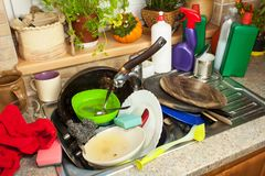 Dirty dishes in the sink after family celebrations. Home cleaning the kitchen. Cluttered dishes in the sink. Housework. Stock Photography