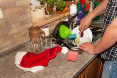 Dirty dishes in the sink after family celebrations. Home cleaning the kitchen. Cluttered dishes in the sink. Housework. Stock Photos