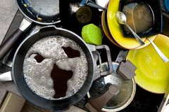 Dirty dishes in sink and foam screaming face Stock Photo