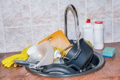 Dirty dishes in the sink in the kitchen . Dirty dishes in the sink in the kitchen on the background tiles stock image
