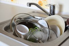 Dirty dishes and unwashed kitchen appliances filled the kitchen. Sink Royalty Free Stock Image