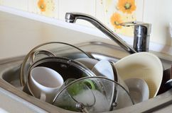 Dirty dishes and unwashed kitchen appliances filled the kitchen. Sink Royalty Free Stock Images