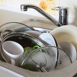 Dirty dishes and unwashed kitchen appliances filled the kitchen. Sink Stock Photo