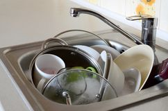 Dirty dishes and unwashed kitchen appliances filled the kitchen. Sink Royalty Free Stock Photos