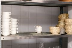 Dirty dishes, wine glasses, plates, cups on metal rack in the restaurant's kitchen stock photos