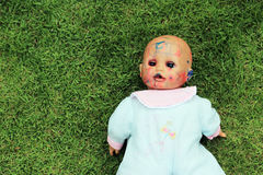 Dirty doll on the grass Royalty Free Stock Image